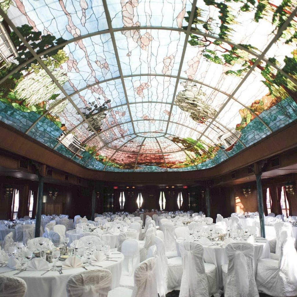 wedding reception setup with white chairs and tables under a stained-glass ceiling at the bahia resort hotel venue in san diego