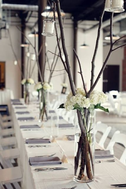 branches and flowers in clear vase centerpieces arranged on a wedding reception table
