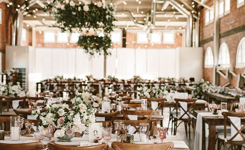 indoor wedding reception setup with flowers, wood chairs, and white drapes at brick venue in san diego