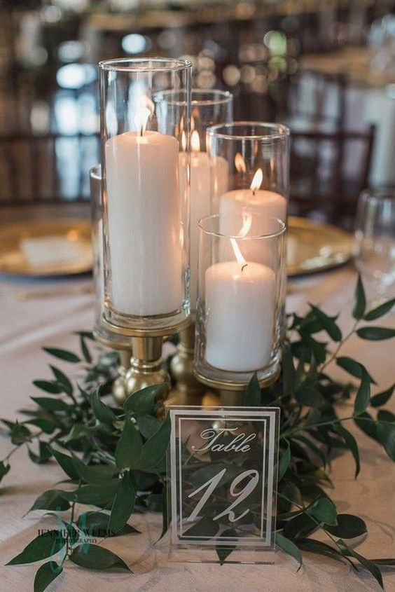 candles in clear candleholders and greenery arranged on a wedding reception table