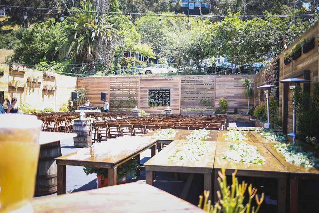 outdoor wedding reception setup at lot 8 in san diego surrounded by wood and greenery