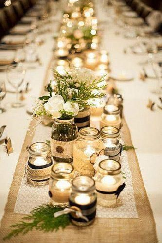 mason jars filled with candles lined up as a centerpiece at a wedding reception table