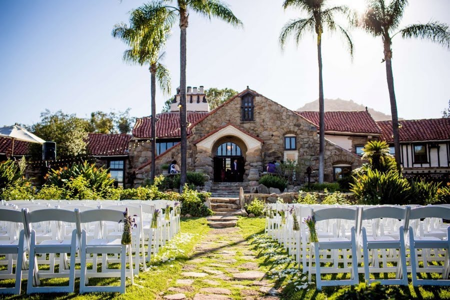 outdoor wedding ceremony setup with white chairs in front of palm trees at mt. woodson castle in san diego
