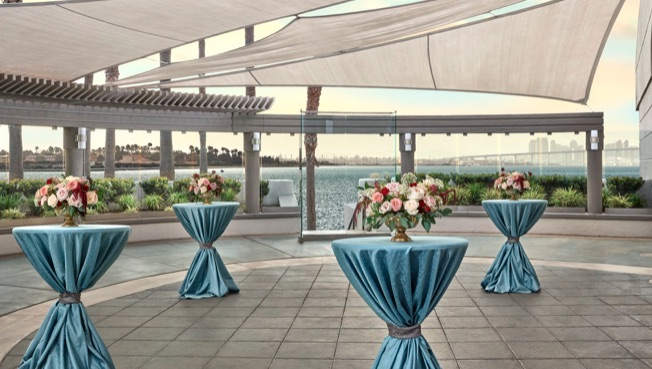 cocktail hour setup with small blue tables and flowers at the sunset terrace at lowes coronado bay resort in san diego