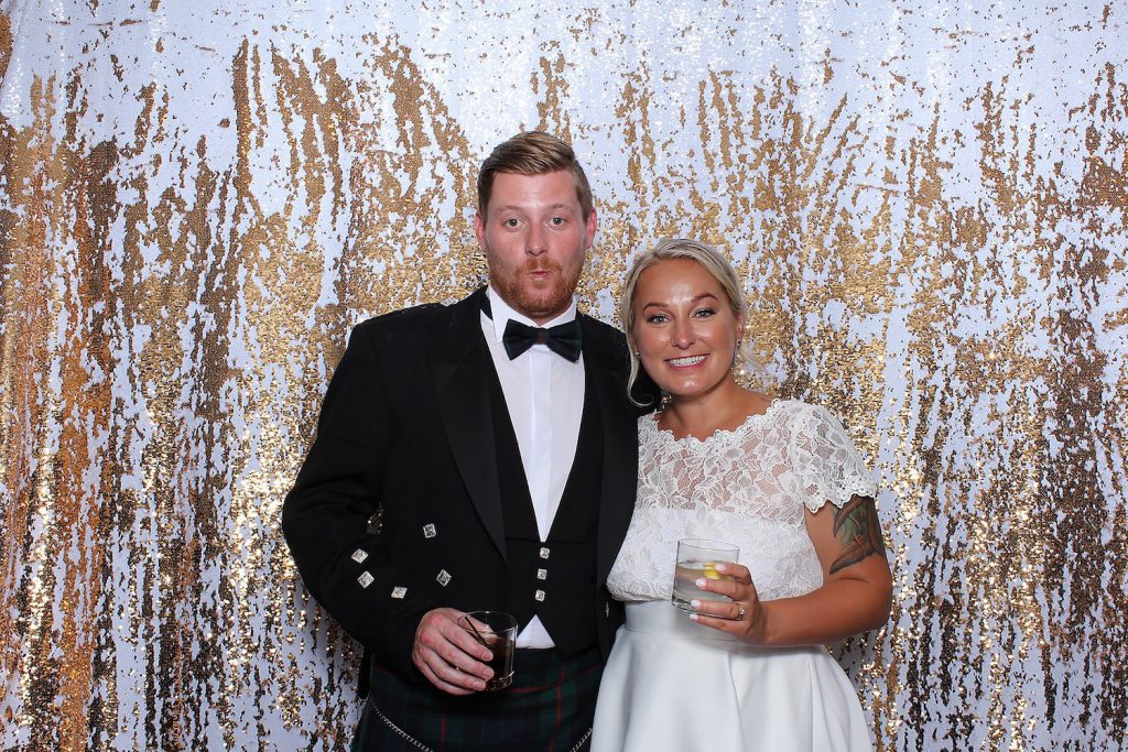 married couple stand in front of customized gold photo booth for a photo