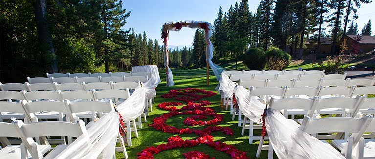 white chairs, an arch, and a rose-petal-covered aisle set up for a wedding on the golf course at the chateau at incline village